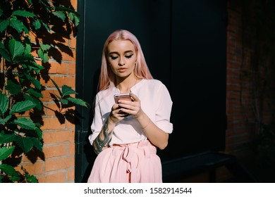 Pensive stylish woman with long pink hairs and tattoo on hand surfing mobile phone nearby black door of bricked building