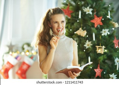 pensive stylish woman with notebook and pen near Christmas tree