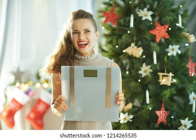 pensive stylish woman with weight scales near Christmas tree