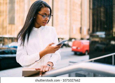 Pensive stylish young woman with dark skinned reading incoming sms on smartphone standing in downtown.African american office worker checking banking account online on cellular via 4G internet