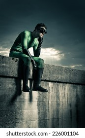 Pensive superhero with hand on chin and dramatic cloudy sky on background.