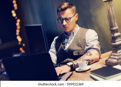 fcc9892c5 Pensive tattooed man in eyeglasses working at home on laptop while sitting  at the wooden table