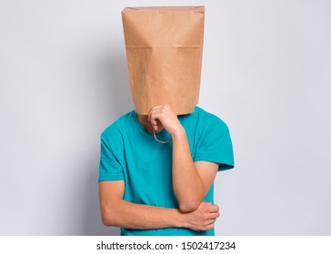 Pensive teen boy with paper bag over head. Thoughtful teenager cover head with bag holding hand near face posing in studio. Child pulling paper bag over head.
