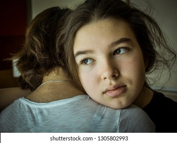 Pensive teen girl put her head on mother's shoulder