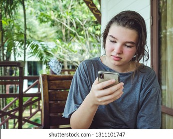 Pensive teen girl with smart phone outdoors portrait
