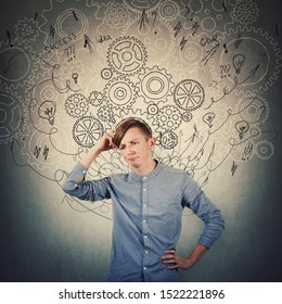 Pensive teenage boy scratching his head looking confused has questions. Perplexed guy thinking of new ideas as gear cogwheels, arrows and mess sketch as thoughts around head. Find solution to problem.