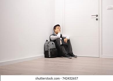 Pensive teenage student sitting in a corner indoors