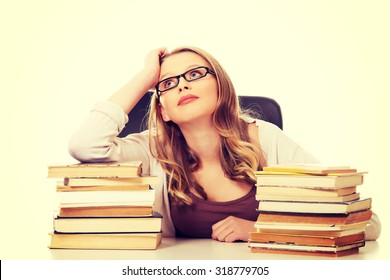 Pensive teenage woman with stack of books