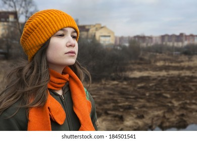 Pensive Teenager in orange knitte? hat and scarf stand alone near the scorched field. Spring time
