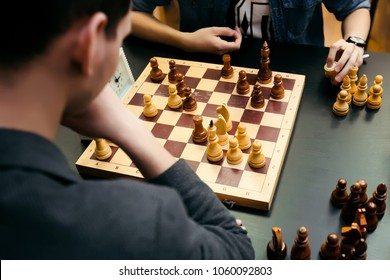 Pensive teenager play chess during chess competition in chess club. Education, chess and mind games.