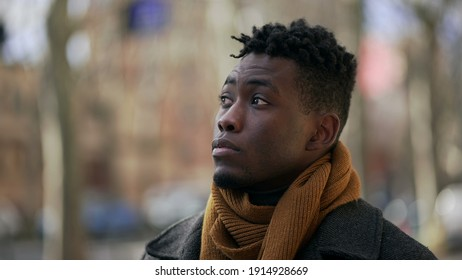 Pensive thoughtful black African man walking outside in winter season