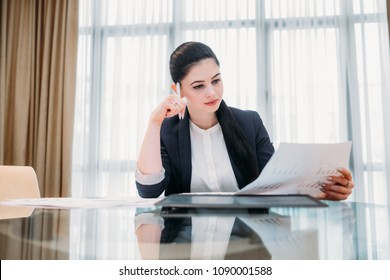 pensive thoughtful business woman reading a document in office workspace. manager analyzing information, assessing results and thinking over company strategy