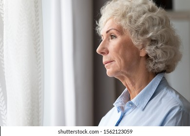 Pensive thoughtful lonely senior adult grandma stand alone at home looking through window waiting, serious sad old elderly woman think of loneliness future feel worried depressed melancholic concept