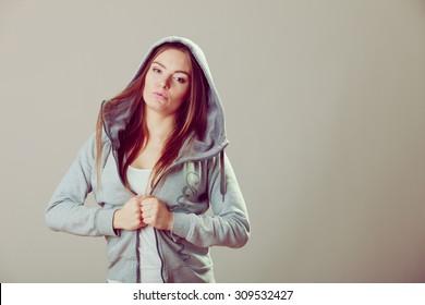 Pensive thoughtful teenager girl wearing sweatshirt with hood and white shirt. Teen fashion. Studio shot.