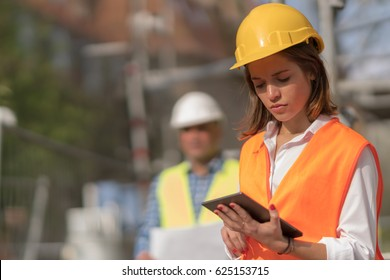 Pensive, thoughtful young civil engineer working with her touchless tablet on construction site