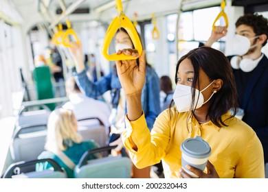 Pensive, müde schwarze Frau, die mit dem Bus pendelt und eine Schutzmaske trägt, die durch eine Koronavirus-Pandemie verursacht wird. Achtsames afrikanisches Mädchen, das Griffe im Bus- oder U-Bahn-Zug hält.