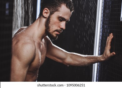 pensive tired young man in shower. tiredness after work. upset man taking a shower