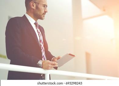 Pensive trendy dressed male entrepreneur using digital tablet and wifi connection for booking tickets for business trip, proud CEO checking work of employee online using application on touchpad