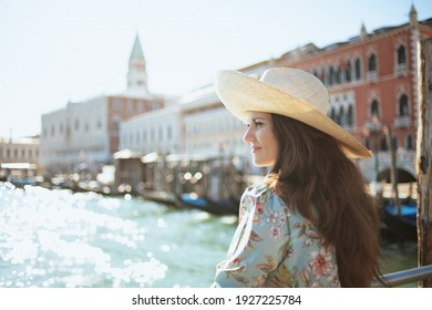 pensive trendy solo tourist woman in floral dress with hat sightseeing on embankment in Venice, Italy.