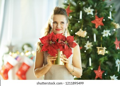 pensive trendy woman with red poinsettia near Christmas tree