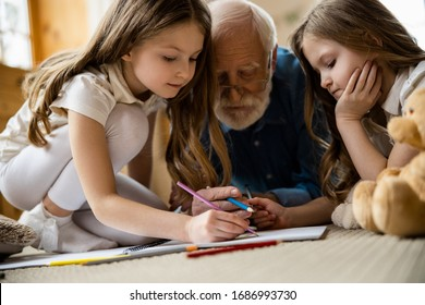 Pensive twin girls sitting comfortably on the carpet and drawing in a sketch book with their grandfather