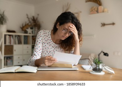 Pensive unhappy young woman sit at desk at home read bad news response in post paper letter. Sad upset female frustrated distressed by negative message or dismissal notice in postal correspondence.