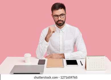 Pensive unshaven man focused aside with thoughtful expression, wears elegant white shirt, thinks about developing business, poses at desktop, uses wireless internet in office. Perfectionism.