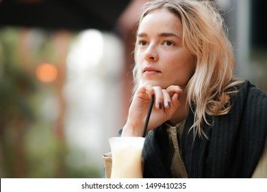 Pensive woman absorbed in thoughts, looking worried with a drink on her table outdoors