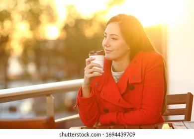 Mujer pescadora sosteniendo una taza de café quitada al atardecer sentada en un balcón