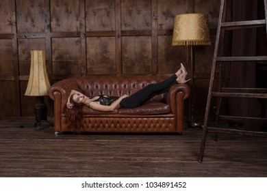 pensive woman lies on the sofa in the Loft style interior. model is dressed in jeans and high heel shoes.