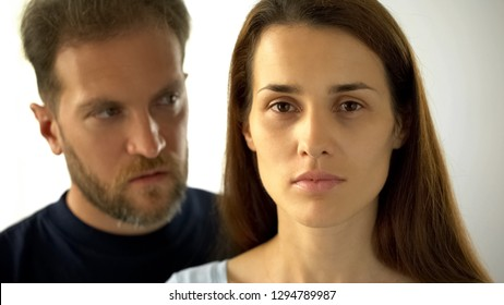 Pensive woman looking at camera man behind wife, inability to make own decisions