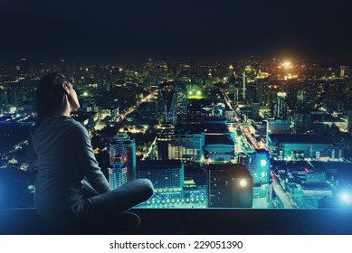 Pensive woman is looking at night city