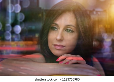 pensive woman looks at the city