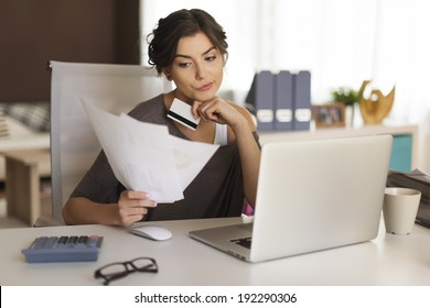 Pensive woman paying bills at home