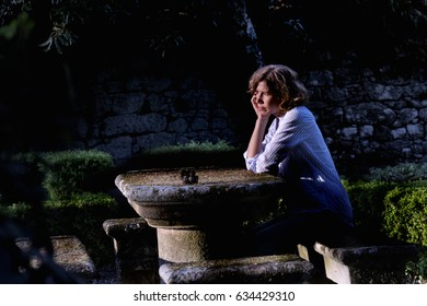 Pensive woman sitting in a park