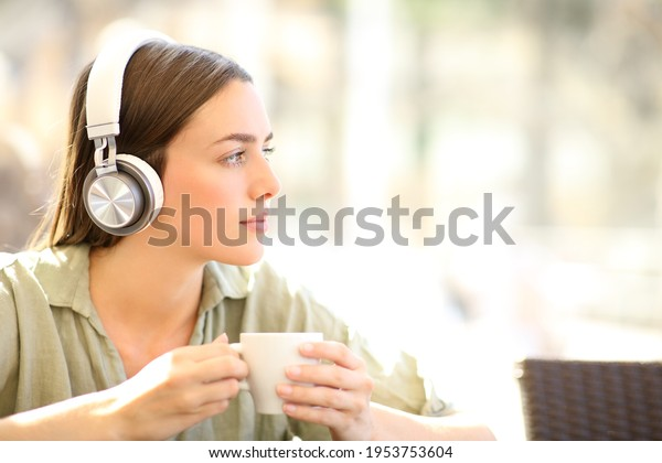Pensive woman wearing wireless headphones relaxing listening to music holding mug in a coffee shop
