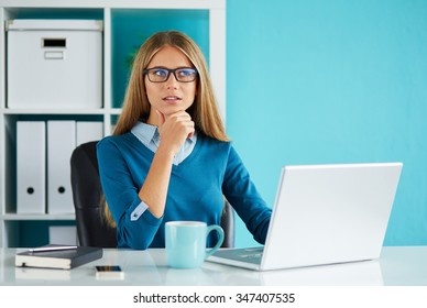 Pensive woman working in modern office on computer
