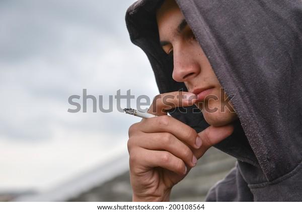 pensive and worried teenage boy with black hoodie is smoking cigarette outdoor. Harmful smoking concept