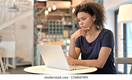 Pensive Young African Woman using Laptop in Cafe