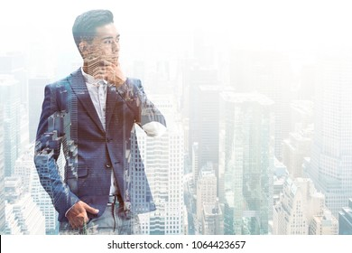 Pensive young Asian businessman wearing a dark suit is thinking standing against a gray city background. Mock up double exposure