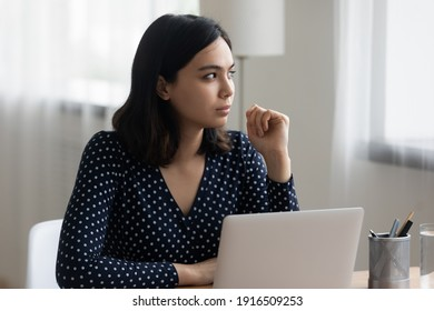 Pensive young asian woman sit at office desk by laptop think on answer the question create business email concept. Thoughtful vietnamese female look aside solve problem in mind visualize work result