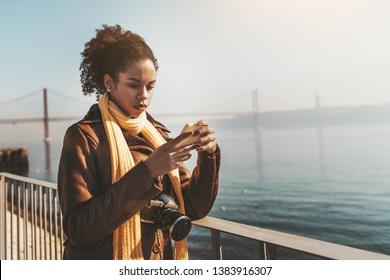 A pensive young biracial female tourist is leaning against an iron fence outdoors on the quayside while answering a message via the smartphone about her travel, with a bridge in the background