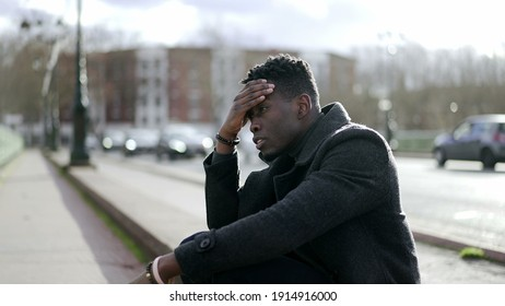 Pensive young black African man standing outside thinking