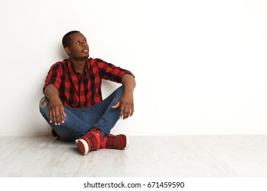 Pensive young black man in casual looking aside at white studio background. Boy in checkered shirt sitting with crossed legs