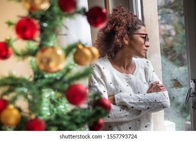 Pensive young black woman celebrating Christmas alone