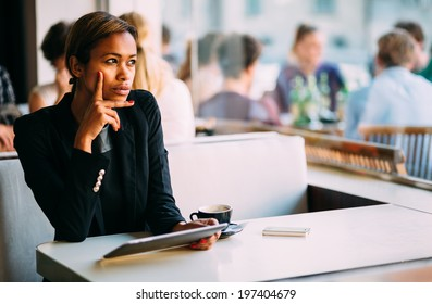 Pensive young black woman using tablet computer in coffee shop