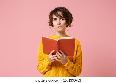 Pensive young brunette woman girl in yellow sweater posing isolated on pink wall background, studio portrait. People sincere emotions lifestyle concept. Mock up copy space. Holding and reading book