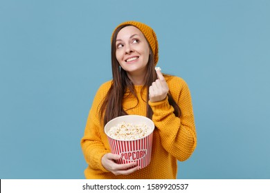 Pensive young brunette woman girl in sweater and hat posing isolated on blue background. People emotions in cinema lifestyle concept. Mock up copy space. Watching movie film holding bucket of popcorn