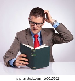 pensive young business man reding a book and scratching his head. on a gray background