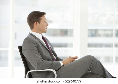 Pensive young businessman sitting on a chair and looking away